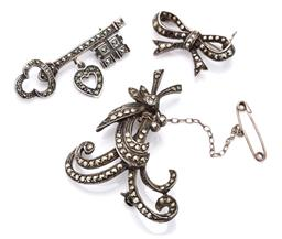 Sale 9115 - Lot 339 - THREE VINTAGE SILVER MARCASITE BROOCHES; key with articulated heart, spray and bow (some missing stones), sizes 38, 46 & 27mm, total...