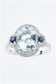 Sale 8299J - Lot 311 - AN 18CT WHITE GOLD AQUMARINE AND GEMSET DRESS RING; featuring an oval cut pale blue aquamarine of 3.10ct and two round cut blue sapp...